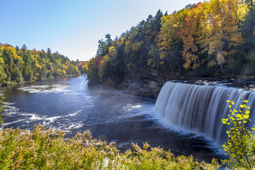 Tahquamenon Falls in Michigan's eastern Upper Peninsula seen with colorful fall foliage. This beautiful waterfall is said to be the second largest in the United States east of the Mississippi River.