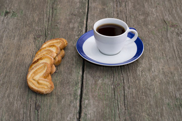 cup of coffee on a saucer with a blue border and cookies in a ro