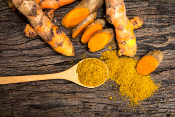turmeric powder in spoon and roots on wooden plate