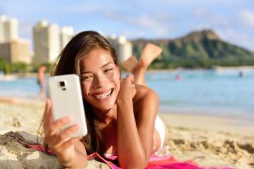 Smartphone woman using smart phone app on beach
