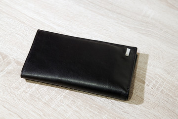 Brown leather wallet on wooden desk background