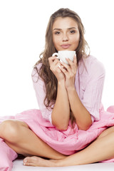 satisfied young woman sitting in bed with a cup of coffee in her hands