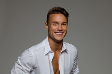 Smiling young man in white unbuttoned shirt. Studio portrait on gray background.
