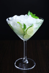Glass of cocktail with ice on dark background