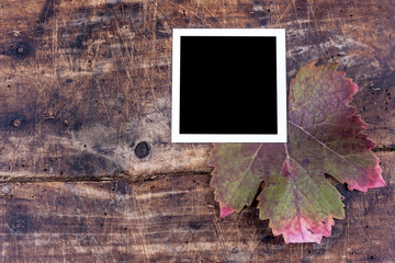 Photo frame with autumn leaf on wooden table