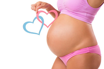 Close-up of a pregnant belly with pink and blue hearts. Guess the sex of the baby-child: girl, boy or twins.