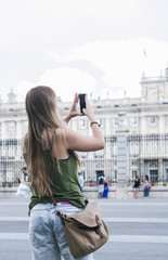 Beautiful young blond woman taking pictures of the Royal Palace in Madrid.