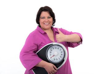 Übergewichtige Frau mit Waage freut sich über ihren Erfolg