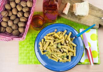 Pasta al pesto di pistacchio, cestino con noci e tagliere di formaggio