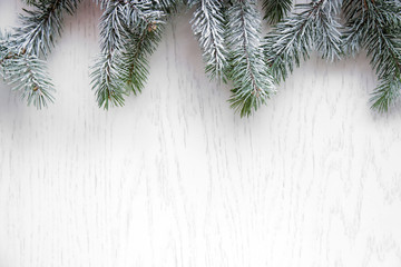 Christmas tree with frost on old wooden table
