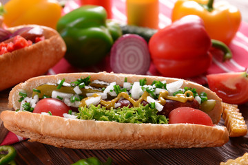 Hot dogs and vegetables on wooden table