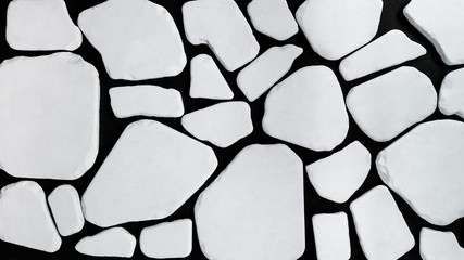 Image of a mosaic made of different seamless pieces of a white stone. They are flat and smooth, and are arranged on a black surface.