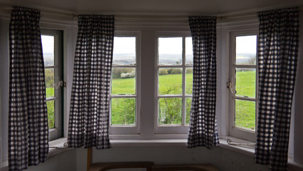 Rustic window with curtains with view of countryside
