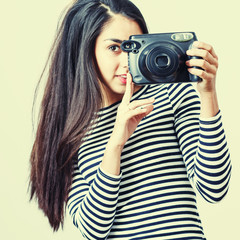 Young girl wearing casual cloth posing with instant camera.