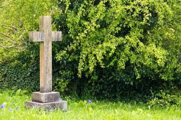 Single cross tombstone in graveyard