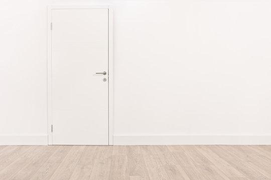 White door and a light brown hardwood floor