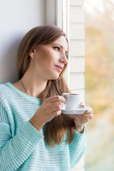 Young beautiful caucasian woman drinking her espresso at window sill