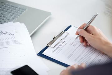 Business woman filling partnership agreement