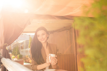 Charming young woman enjoying tea in cafe