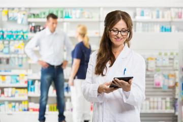 Female Pharmacist Holding Digital Tablet At Pharmacy