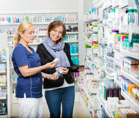 Customer Standing By Chemist Showing Medicines In Pharmacy