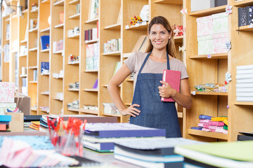Saleswoman With Hand On Hip Holding Book