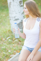 Selective focus on pretty young blond-haired woman wearing white T-shirt standing aside drinking water and smiling satisfied with her life. Park on background