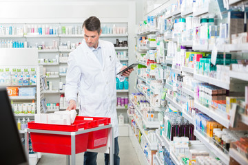 Male Pharmacist Counting Stock While Holding Digital Tablet