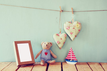 wooden boat toy and teddy bear over wood table next to blank photo frame and fabric hearts. retro filtered image