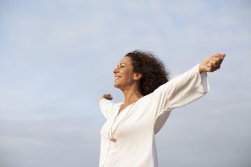 Mujer madura feliz con los brazos abiertos al cielo
