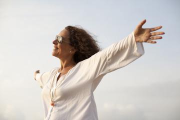 Mujer con los brazos abiertos hacia el sol