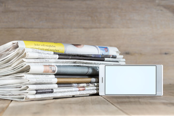 smartphone template and stack of newspapers displaying current i