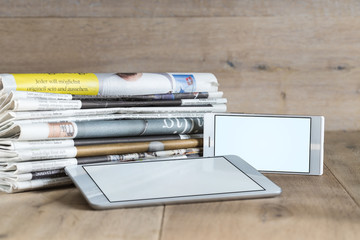 Blanl tablet and smartphone templates and stack of newspapers di