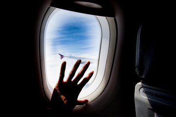 passenger hand touch window of airplane,silhouette
