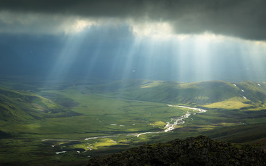 Fotomurales - Sun rays shining through the dark clouds and shining on a river in Iceland.