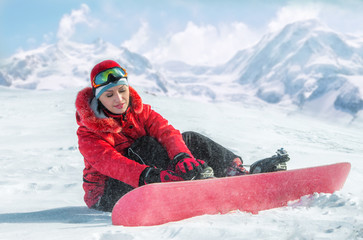 Woman with snowboard sitting in the snow