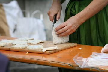 Frau im Dirndl schneidet Käse in Scheiben