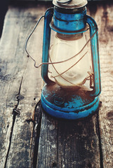 Vintage Dirty Blue Oil lantern on Wooden Background