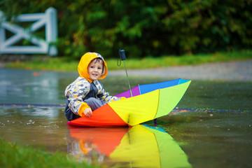 Cute boy with colorful rainbow umbrella on a rainy day, having f