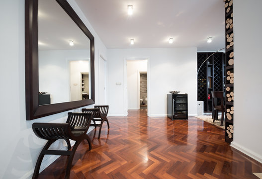 Spacious anteroom interior with large mirror and shiny brown par
