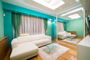 Interior of a modern green living room with luxury ceiling light