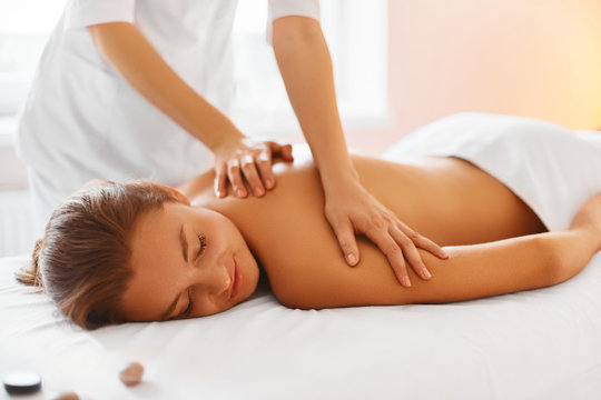 Spa treatment. Woman enjoying massage in spa centre.