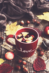 Apple and cranberry tea in red cup, warming scarf, apples, nuts