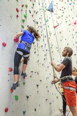 junge Frau beim Klettern in der Halle