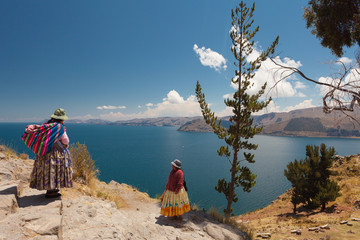 Foto op Aluminium Meer / Vijver Two Women In Traditional Bolivian Clothes Standing On The Rock Close To The Titicaca Lake.