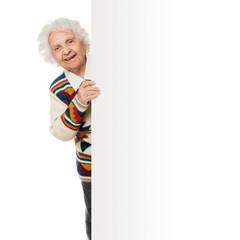 elderly woman alongside of ad board