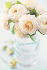 Beautiful fresh roses in a vase on a table . light background .