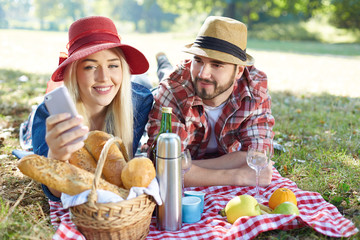 Composite of Couple taking selfie on smartphone on romantic picn