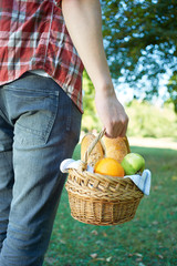 Man holding a basket with an bread on picnic