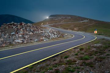 Driving on winding asphalt road at night